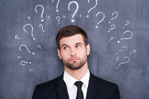 Confused man surrounded by question marks