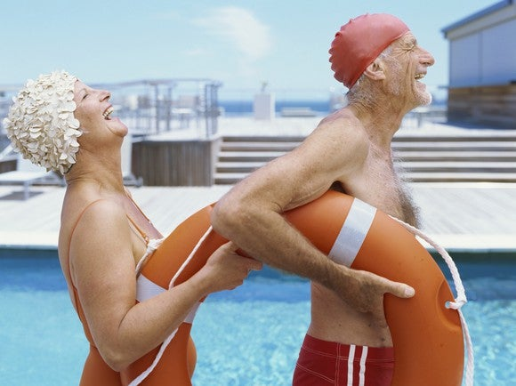 A senior man and woman laughing next to a pool.
