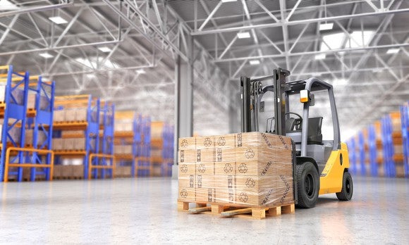 Forklift with pallet of boxed goods in a warehouse.
