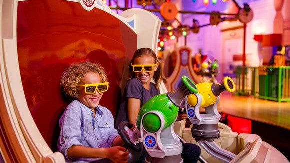 Two young riders on Toy Story's Midway Mania attraction wearing yellow 3D glasses.