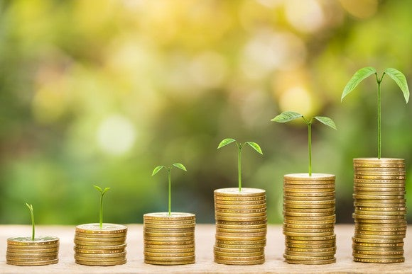 Plants growing on coins stacked beside each other to depict dividend growth stocks.