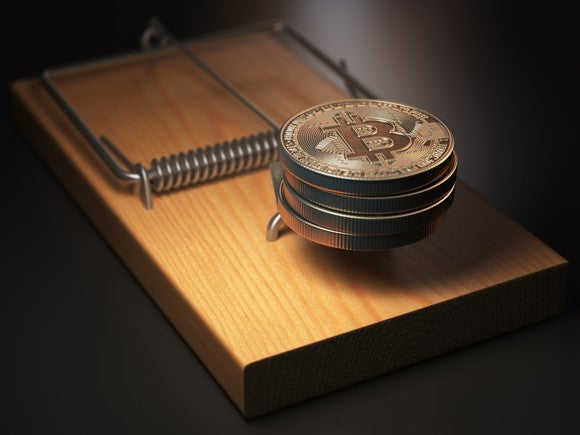 Physical gold bitcoins in a mouse trap.
