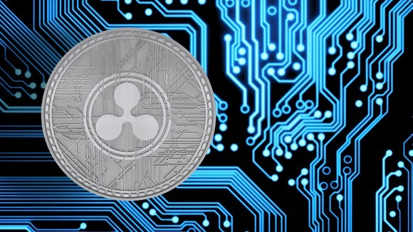 A physical silver XRP coin next to circuitry.
