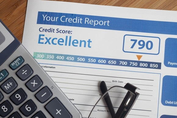 A credit report with an excellent score lying next to a calculator and a pair or reading glasses.