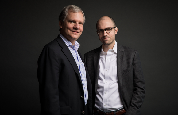 Arthur Sulzberger, Jr. and A. G. Sulzberger pose in suits for a professional photo with a black background.