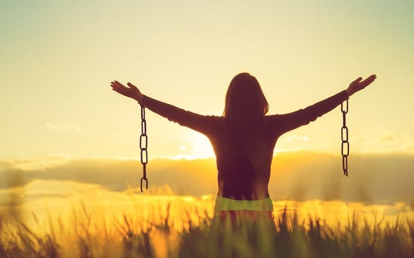 Woman in a field with arms raised, facing the sun, with shackles coming down from her wrists
