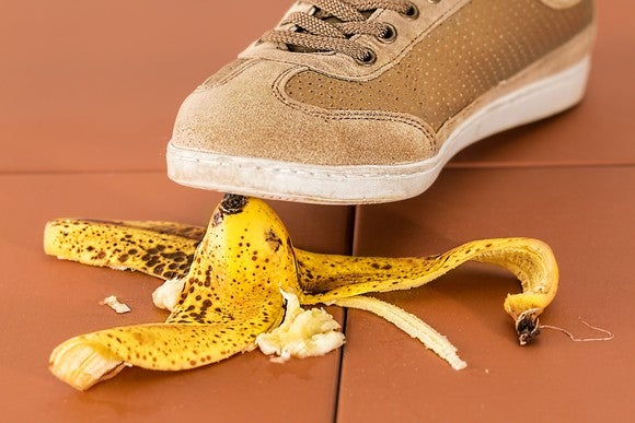 A close-up of a sneaker stepping on a banana peel
