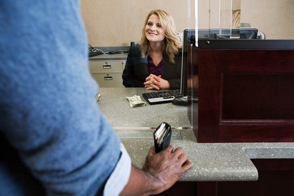 Bank teller greeting a customer who's holding a wallet full of cash.