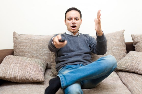 A man appears to be angry at his television.