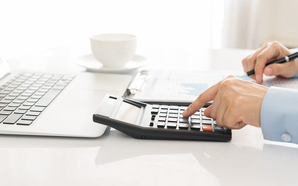 Man using a calculator next to a laptop and a cup with a saucer.