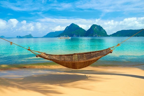 A hammock on a sandy beach overlooking a bright blue tropical lagoon and green mountains in the background.