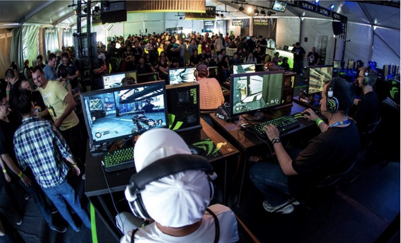 A crowd watches a group of gamers play a video game on PC.
