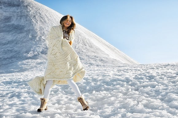 Person wearing white wrap-shawl and fur-lined boots in a snowfield on a clear day.