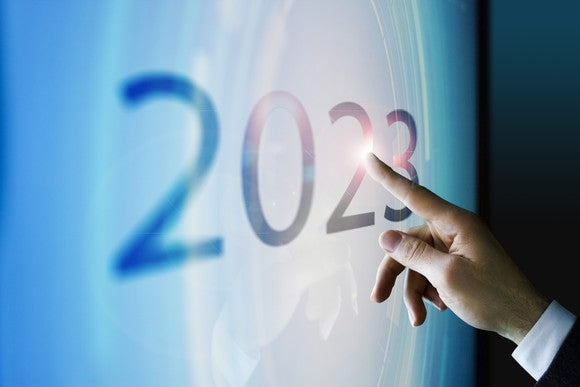 Finger touching a screen displaying the number 2023.