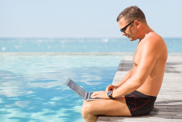 Man in swim trunks using a laptop by a pool