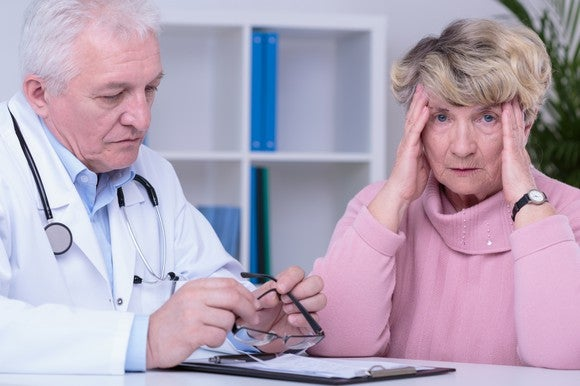 A frustrated senior woman holding her temples with a doctor sitting to her right.