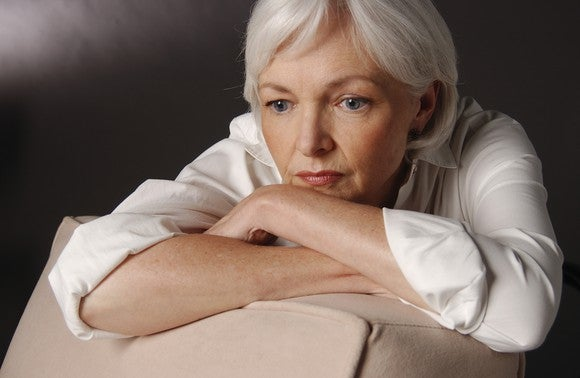 A worried senior woman in deep thought, with her arms crossed on a chair, and her head resting on her arms.