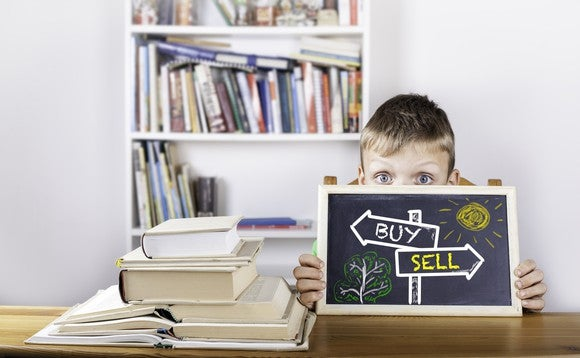 "A boy writes ""buy"" and ""sell"" on a blackboard."