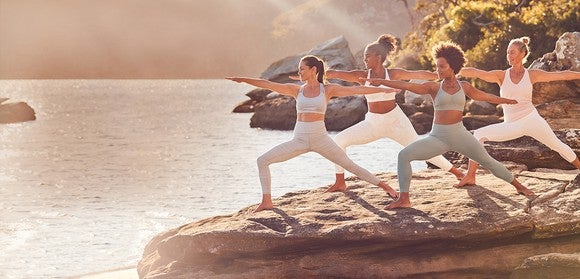 Four women in Athleta apparel striking the same yoga pose on a large rock