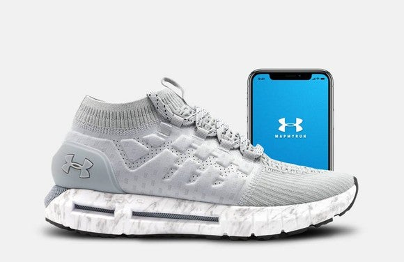 Under Armour's HOVR Phantom shoe shown on a white background with the MapMyRun App shown on a phone behind it.