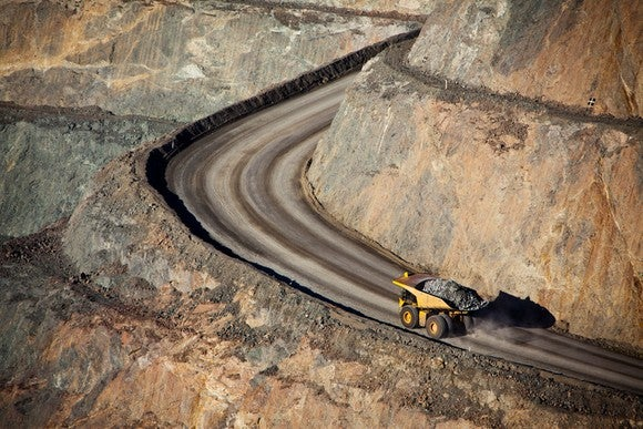 A bird's eye view of a giant earth hauler driving up a road at a gold mine.