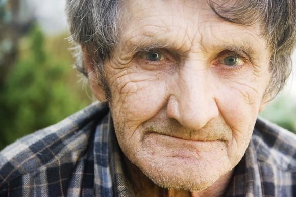 An elderly man in a flannel shirt pensively smirking.