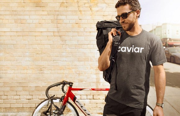A Caviar employee carrying food in a bag over his right shoulder with a bike leaning on the wall behind him.