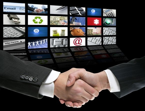 Two businessmen shaking hands in front of a wall of 24 TV screens.