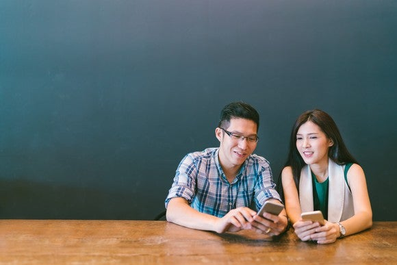 A young couple checks their smartphones.