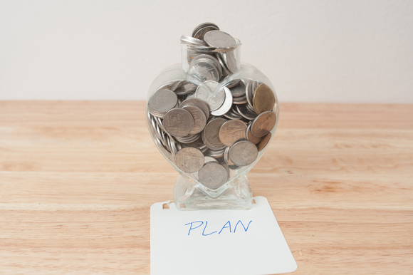 "A jar of coins on top of a notecard that says ""PLAN,"" on a wooden table."