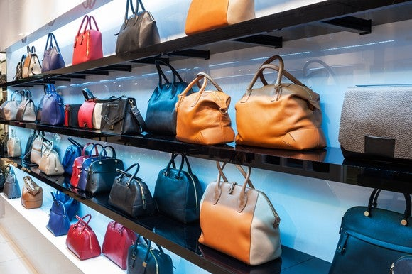 Shelves of high-end handbags in a retail store.