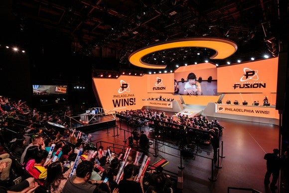 An audience watching a brightly lit stage during an Overwatch League match.