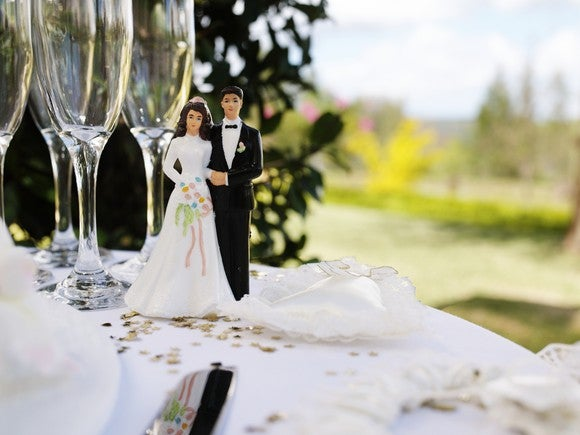 Wedding couple figurine on table with champagne flutes in front of an outside venue.