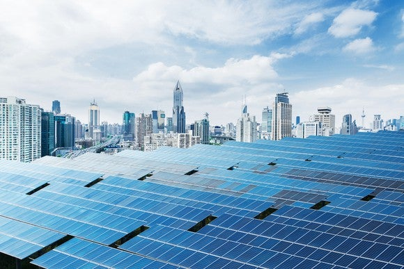 Solar panels with a city in the background.