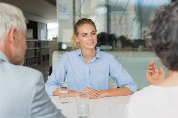 Woman in collared shirt sitting across from man and woman