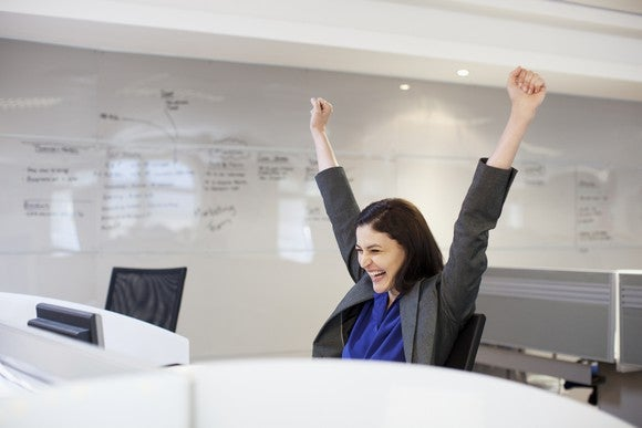 a woman celebrates sitting at her office desk.