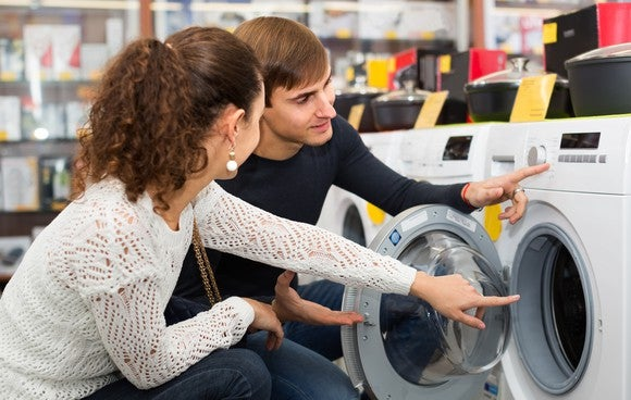 A woman and a man looking at a washing machine in a store