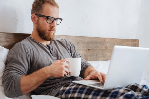 Man in pajamas working on a laptop in bed