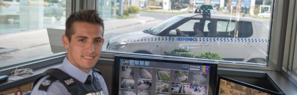 Security guard in glass office with Brink's car outside.