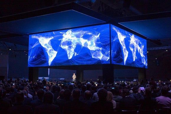 Mark Zuckerberg speaking on stage below Facebook's visualization of a connected world