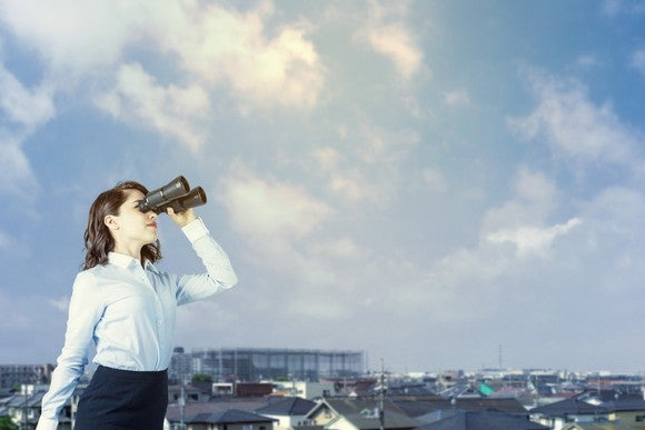 Woman with binoculars looking off into the distance.