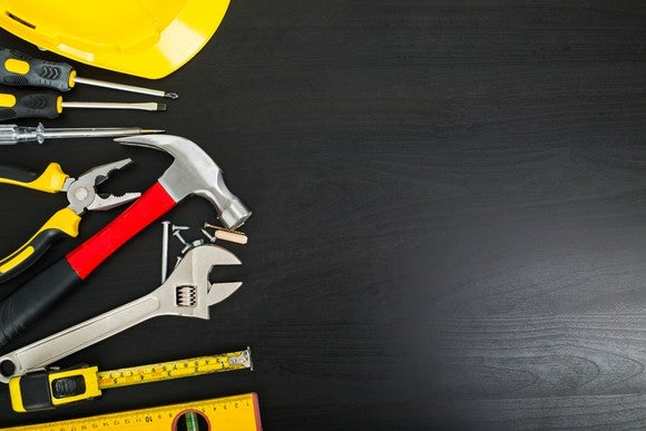 A variety of tools laid out on a black surface.
