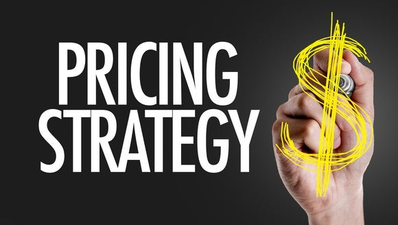 a hand writing the words pricing strategy on a screen