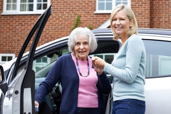 Middle-aged woman helping an older woman out of a vehicle