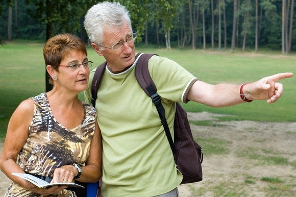 Senior couple outdoors, with woman holding a book and man pointing outward