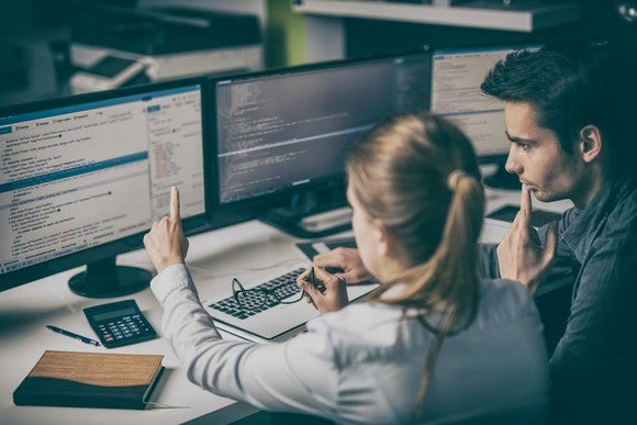 Two people looking at software code