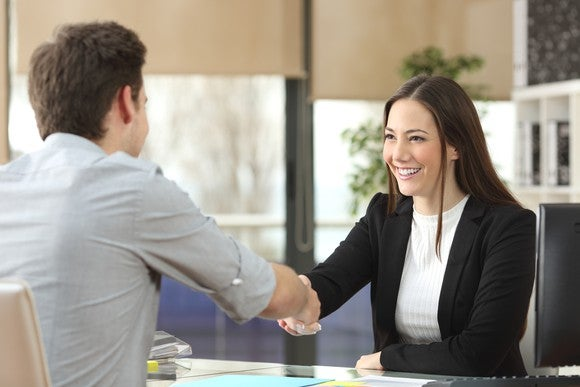 Professionally dressed young woman shaking hands with a man sitting across from her