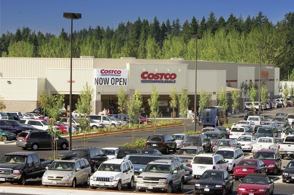 A Costco storefront with a parking lot packed with cars.