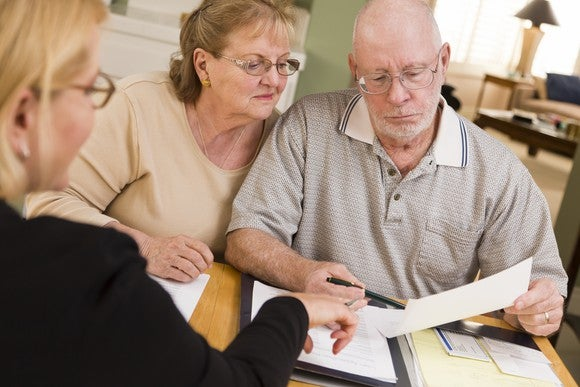 A senior couple discussing paperwork with a financial adviser.