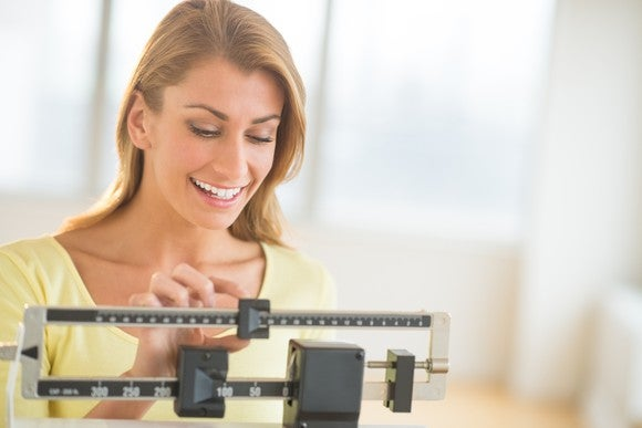 A smiling woman weighing herself on a balance scale.